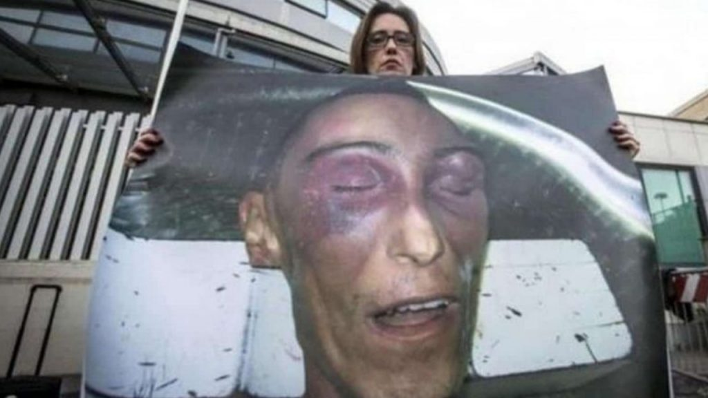 Ilaria Cucchi mentre mostra la fotografia del volto del fratello Stefano poco dopo la sua morte