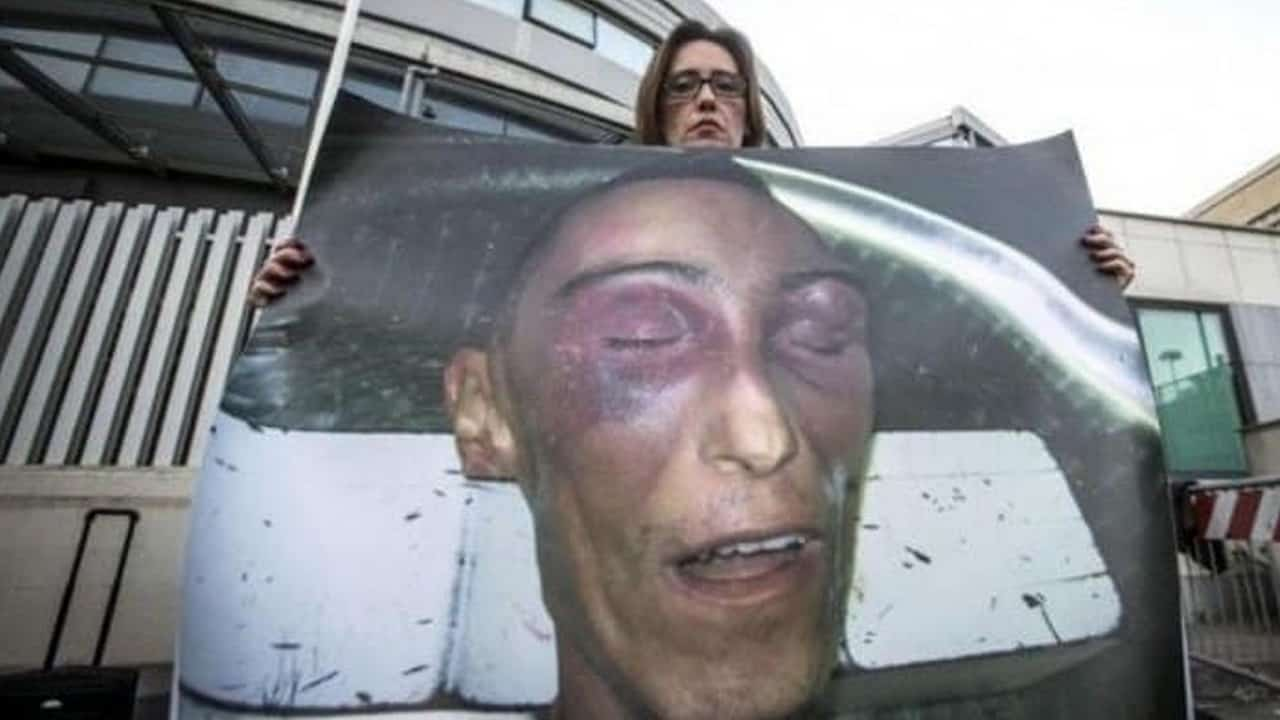 ilaria cucchi con in mano un manifesto con la foto del volto del fratello stefano cucchi