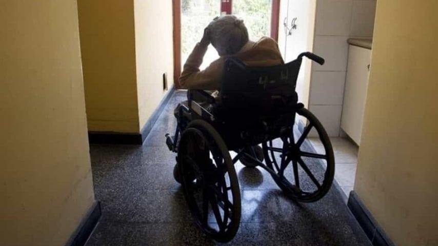 donna anziana di spalle seduta su una sedia a rotelle