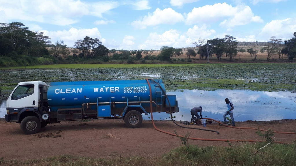 Camion blu con il quale viene riempita una pozza d'acqua