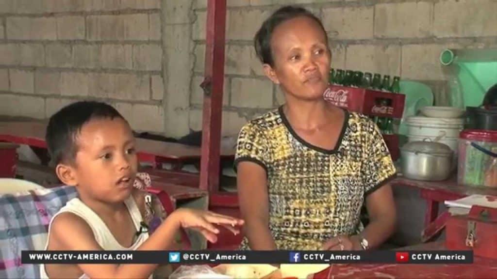 Daniel Cabrera, bimbo filippino di 9 anni costretto a studiare sul marciapiede, qui raffigurato con sua mamma Christina