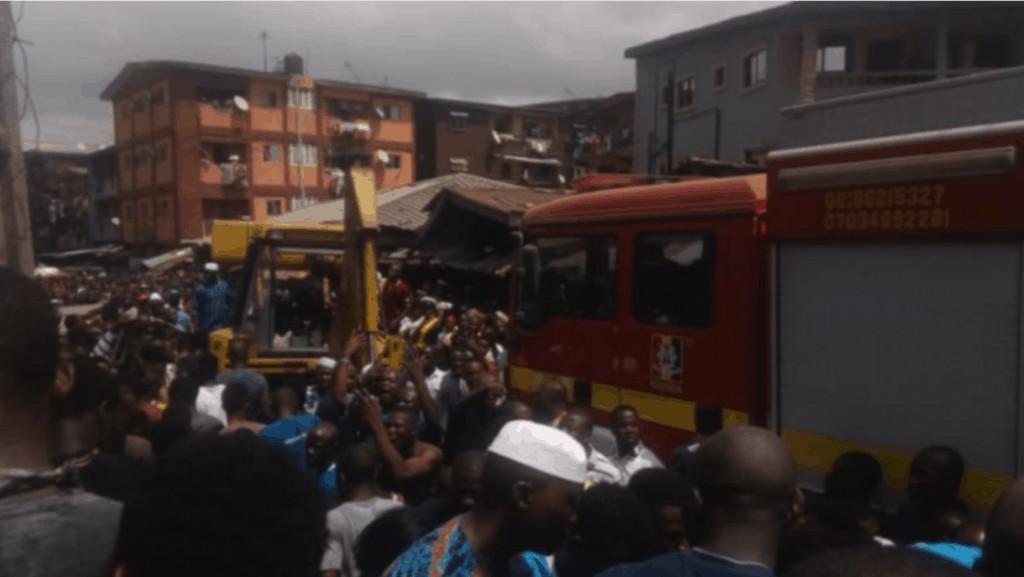 Immagine delle persone che si affollano intorno all'edificio crollato