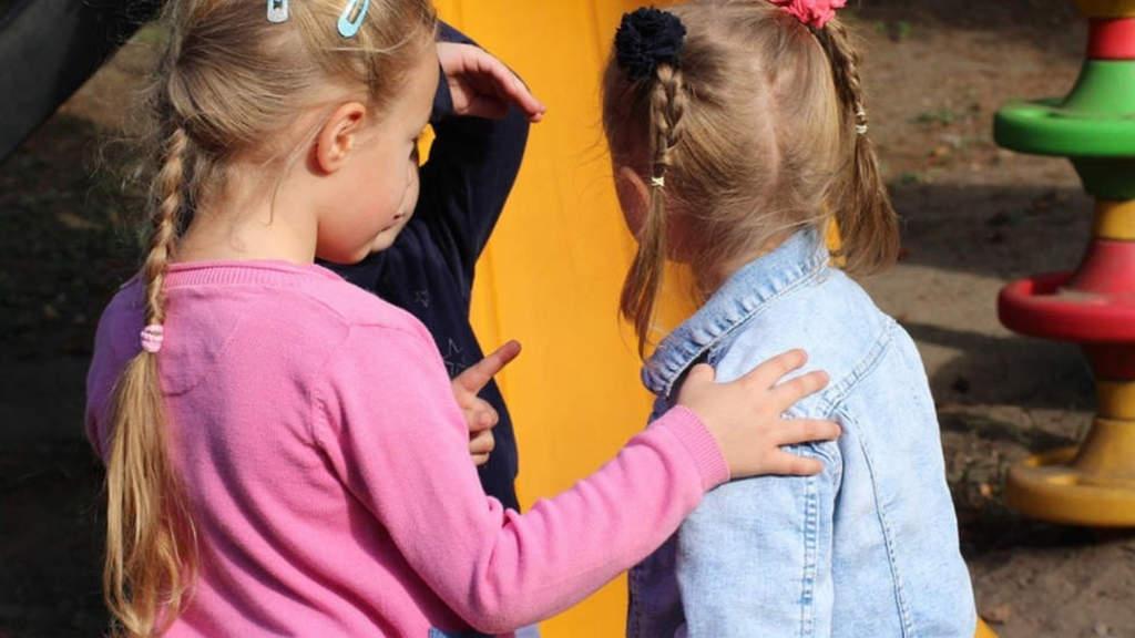 due bambine di spalle davanti a uno scivolo