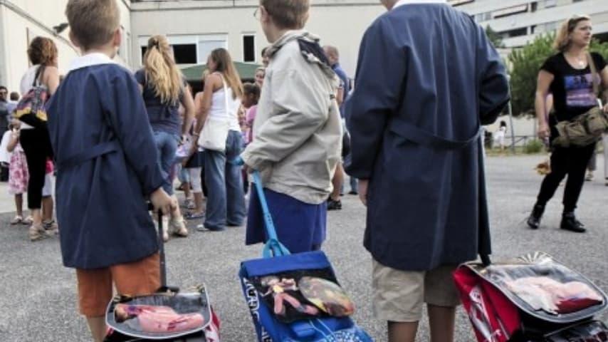bambini con lo zaino fuori da una scuola