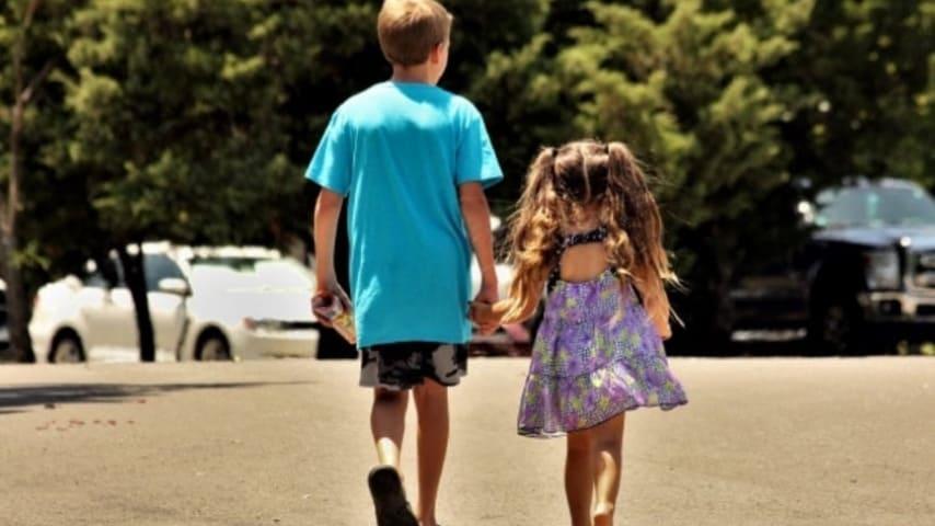 due bambini di spalle che passeggiano mano nella mano