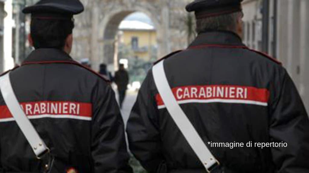 due carabinieri camminano di spalle in uniforme