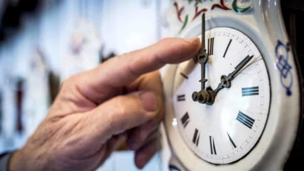 un dito di una persona anziana mentre sposta le lancette su un orologio
