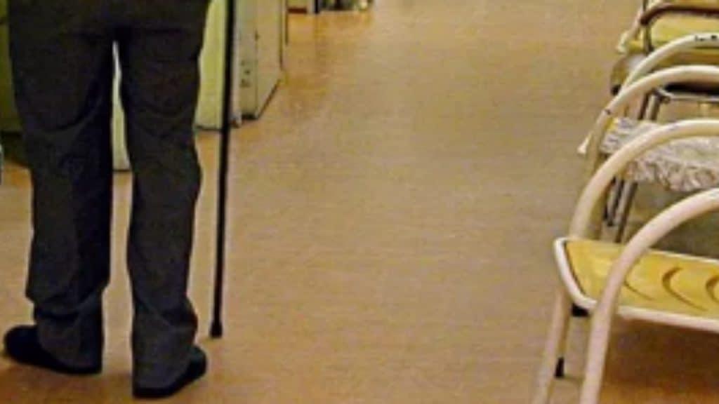 gambe di un anziano con il bastone mentre passeggia in ospedale
