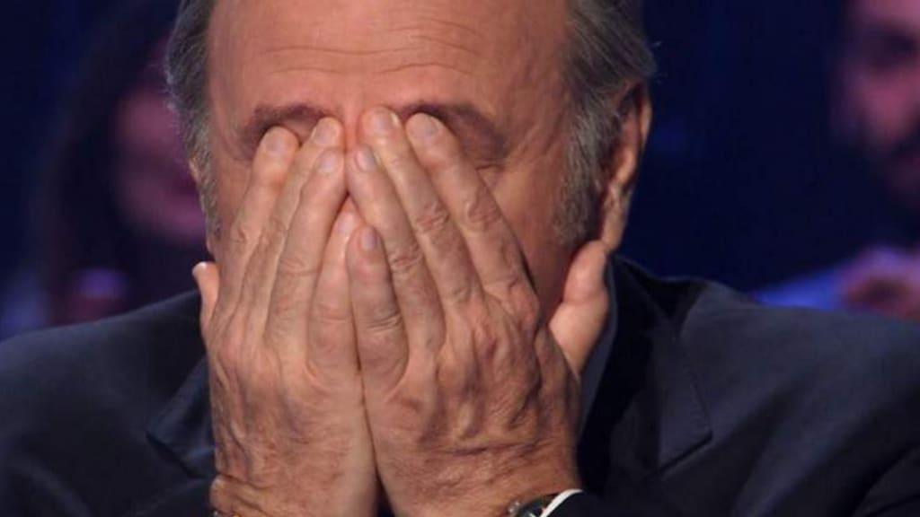 Gerry Scotti mentre trattiene le lacrime nello studio di il milionario