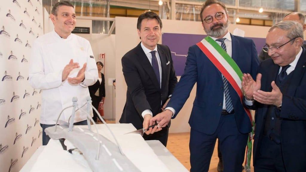 Il primo ministro Giuseppe Conte taglia la torta a forma di ponte per l'inaugurazione dei lavori nello stabilimento Fincantieri