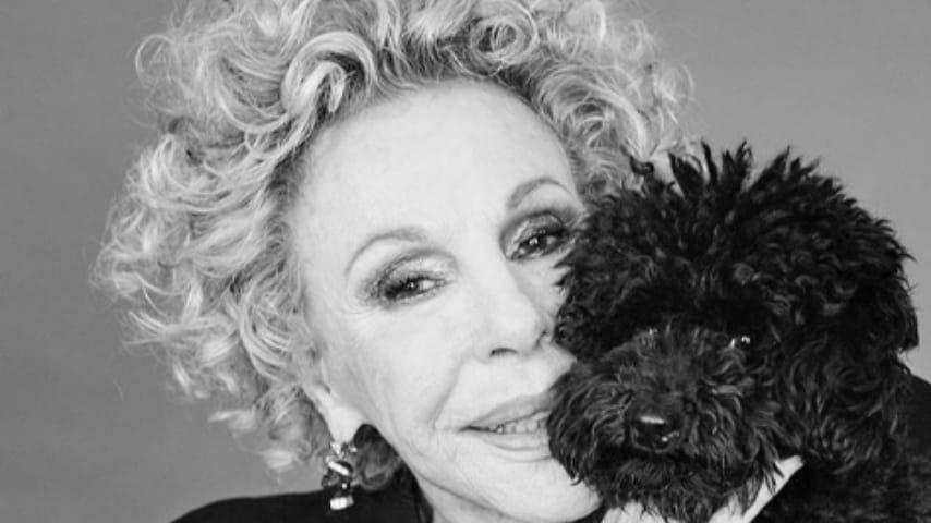 primo piano in bianco e nero di ornella vanoni che abbraccia il suo cane nero