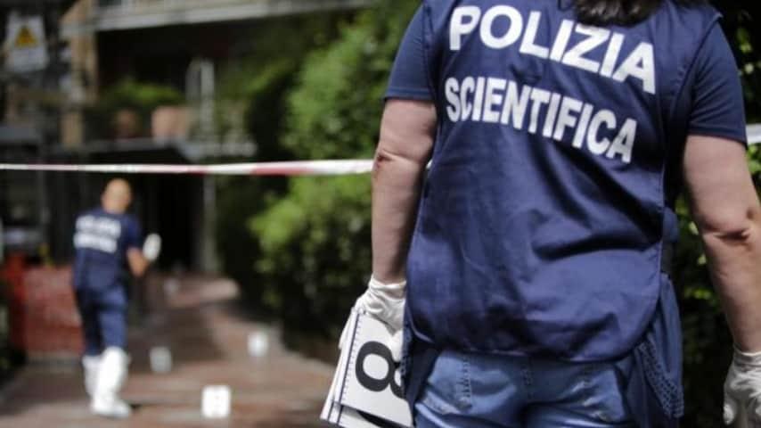 Agente di polizia scientifica di spalle sul luogo del delitto