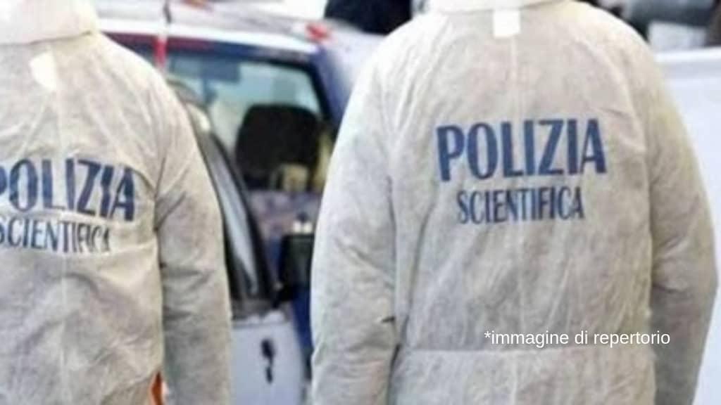 due uomini della polizia scientifica di spalle