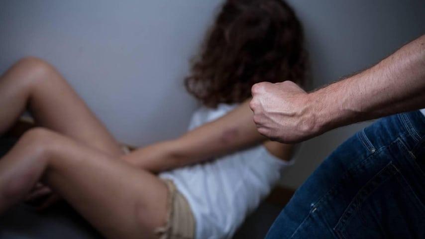 il pugno chiuso di un uomo e una ragazza indifesa sullo sfondo