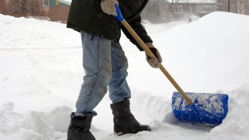 uomo che spala la neve dal viale