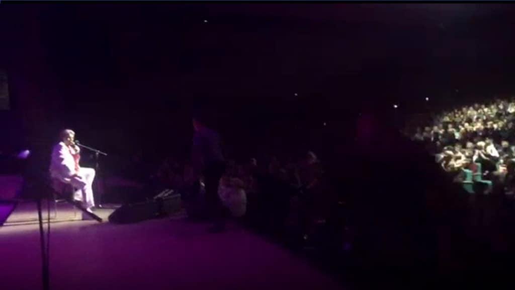 """Toto Cutugno mentre canta """"Un italiano"""", con il contestatore appena salito sul palco"""