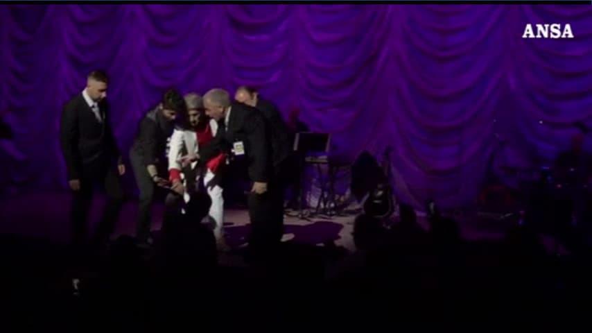 Toto Cutugno, scortato dalla sicurezza, stringe la mano al contestaore, finito giù al palco