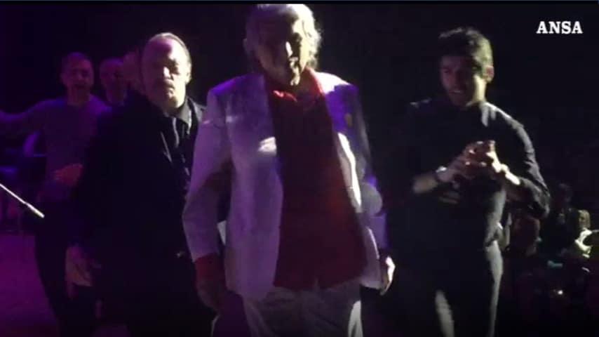 Toto Cutugno esce di scena per la pausa del concerto. Alle sue spalle, il contestatore, che chiede la sua attenzione, fermato dalle guardie