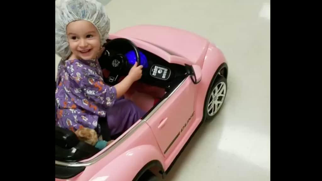Una bimba prova felice la sua mini car rosa per andare in sala operatoria