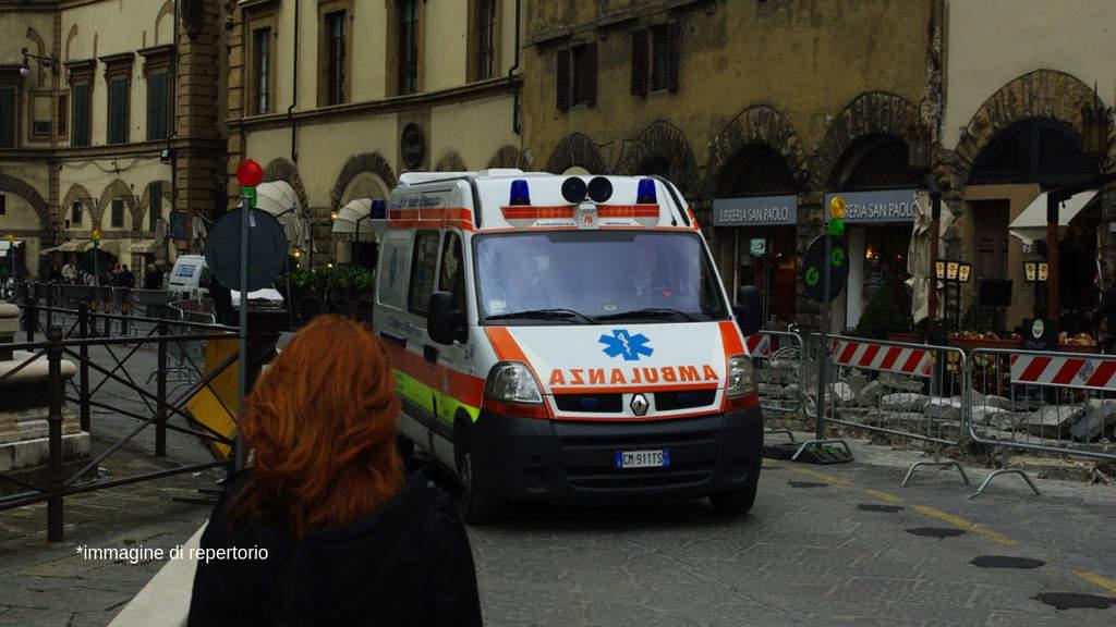 ambulanza in strada di fronte ad una donna di spalle con i capelli rossi