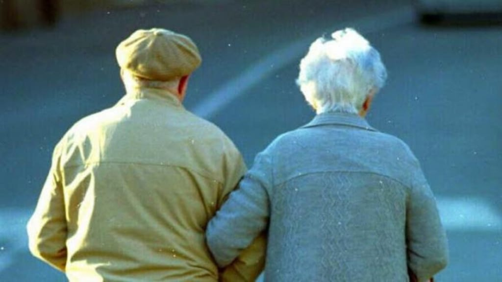 due anziani di spalle che si tengono sotto braccio
