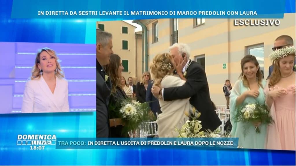 barbara d'urso mentre osserva laura fini e marco predolin vestiti da sposi mentre si baciano