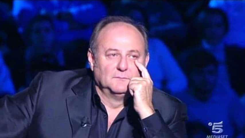 Il conduttore Gerry Scotti commosso piange durante un programma televisivo