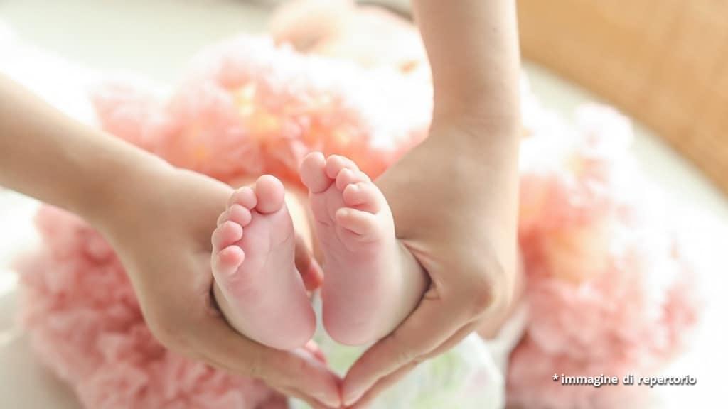 piedini di neonata tenuti da mani di mamma