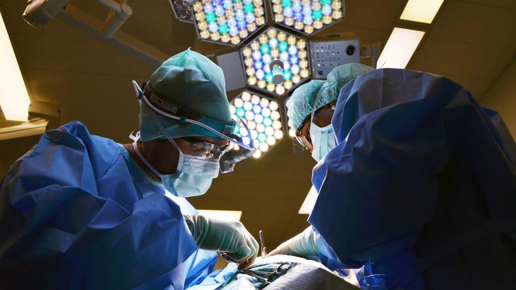 due medici ripresi dal basso mentre operano