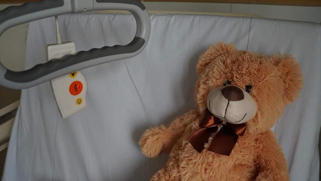 peluche a forma di orso in un letto d'ospedale