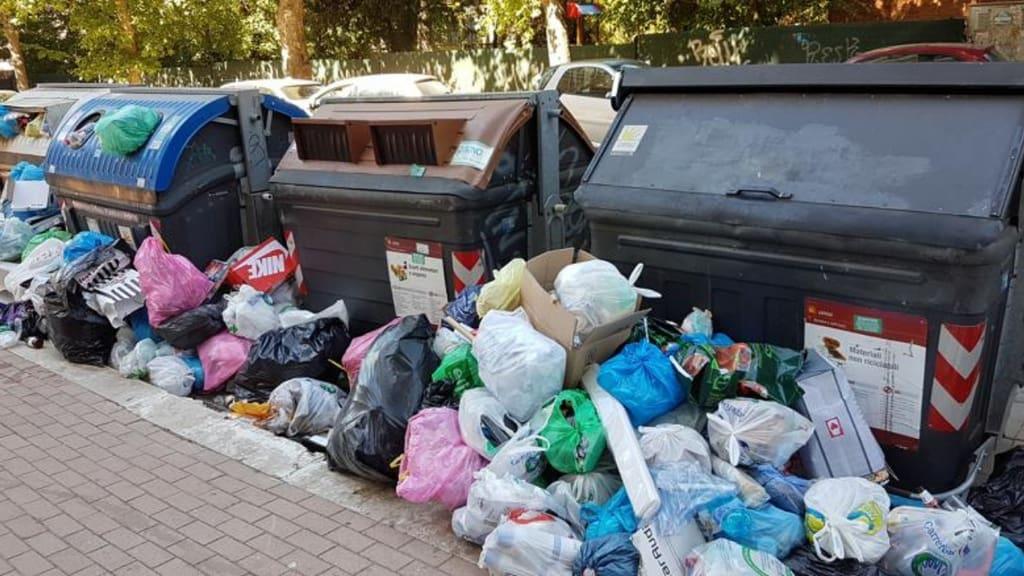sacchetti della spazzatura sovrastano i bidoni dell'immondizia