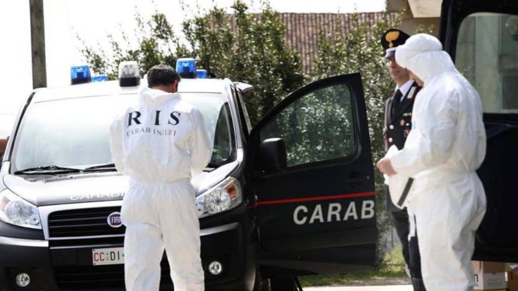 due uomini della scientifica di spalle e una macchina dei carabinieri