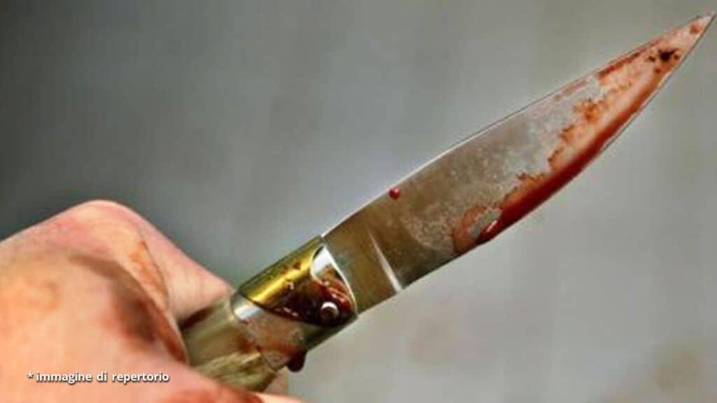 uomo impugna coltello insanguinato