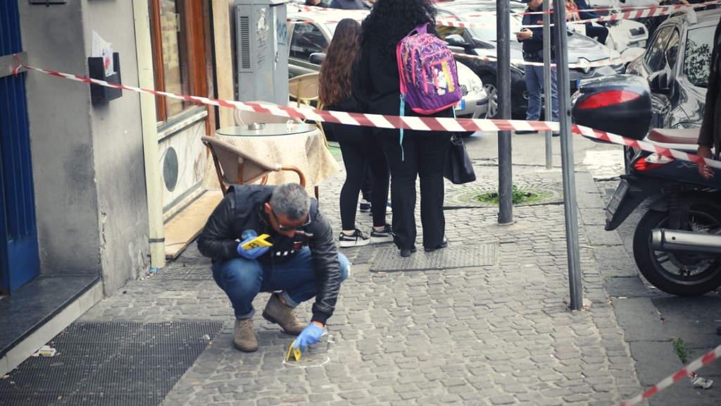 La polizia comincia le indagini dopo la sparatoria raccogliendo prove sulla scena