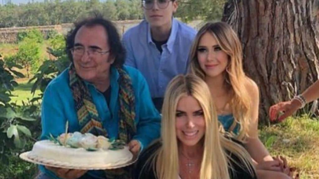 al bano carrisi mentre festeggia con una torta in mano il suo compleanno con affianco i due figli e seduta in basso loredana lecciso