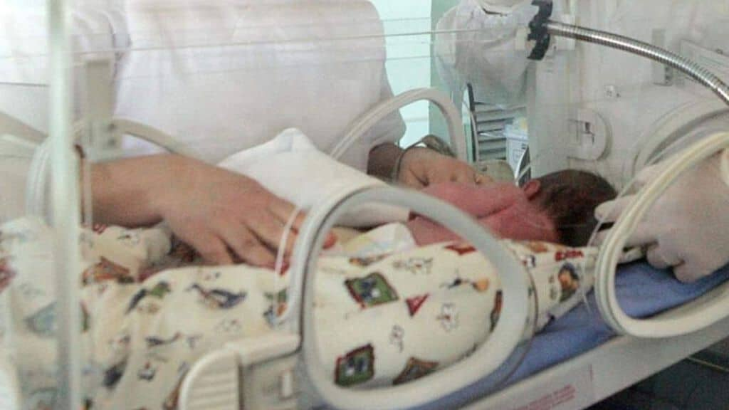 bambino sdraitato dentro incubatrice