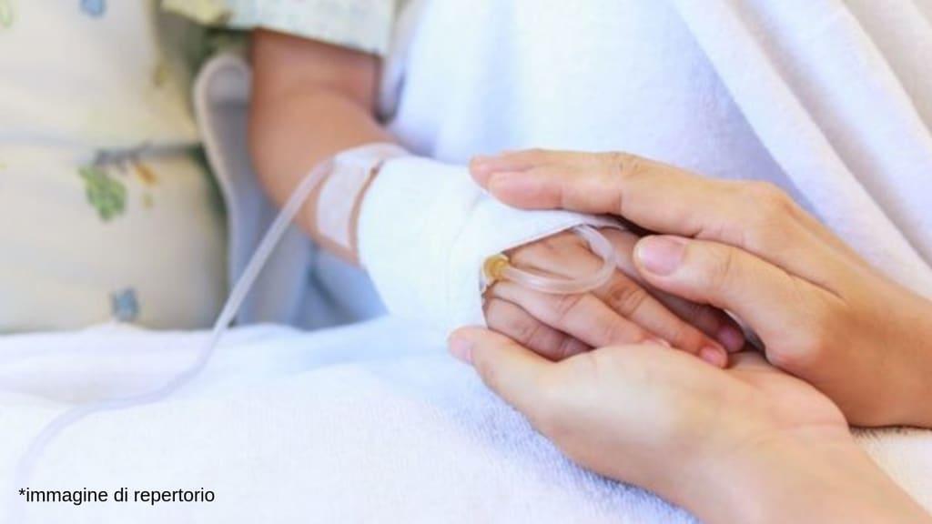 mano di una bimba in ospedale con la flebo