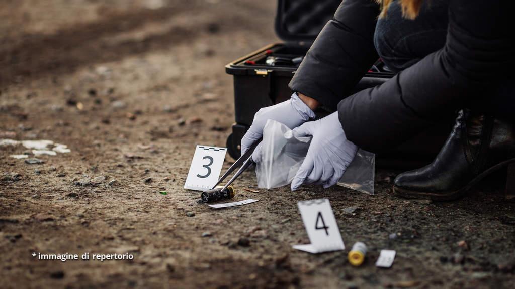 Agente della scientifica intenta a fare dei rilievi su una scena del crimine