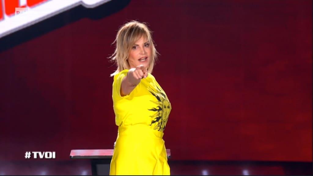 simona ventura vestita di giallo al centro dello studio mentre lancia la pubblicità