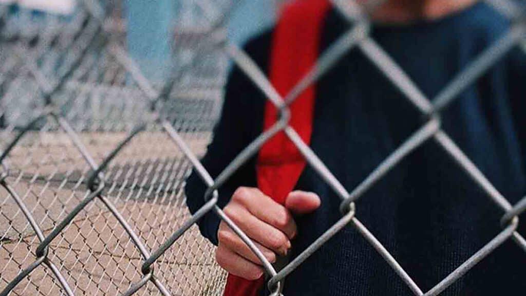 studente di fronte al cancello della scuola