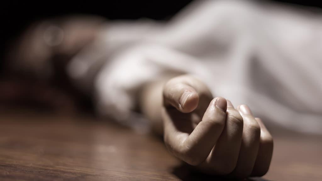 primo piano sulla mano di un cadavere femminile steso a terra