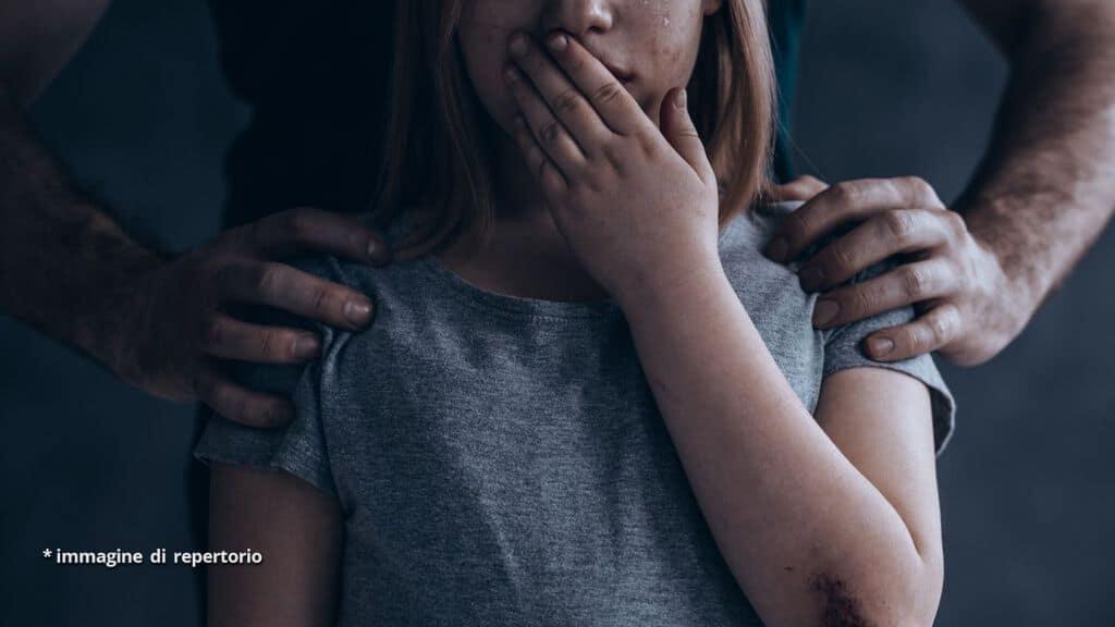bambina che piange con mano di uomo sulla spalla