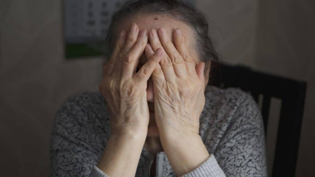 anziana con le mani sul volto