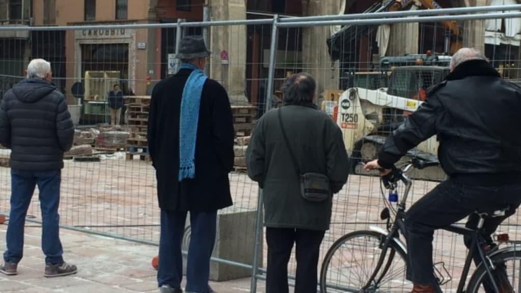 Quattro anziani guardano un cantiere urbano