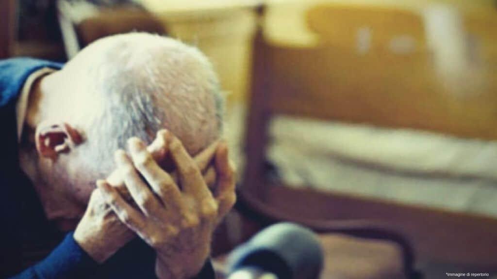 anziano che si tiene la fronte con le mani