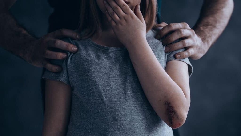 una bambina che si tappa la bocca con la mano