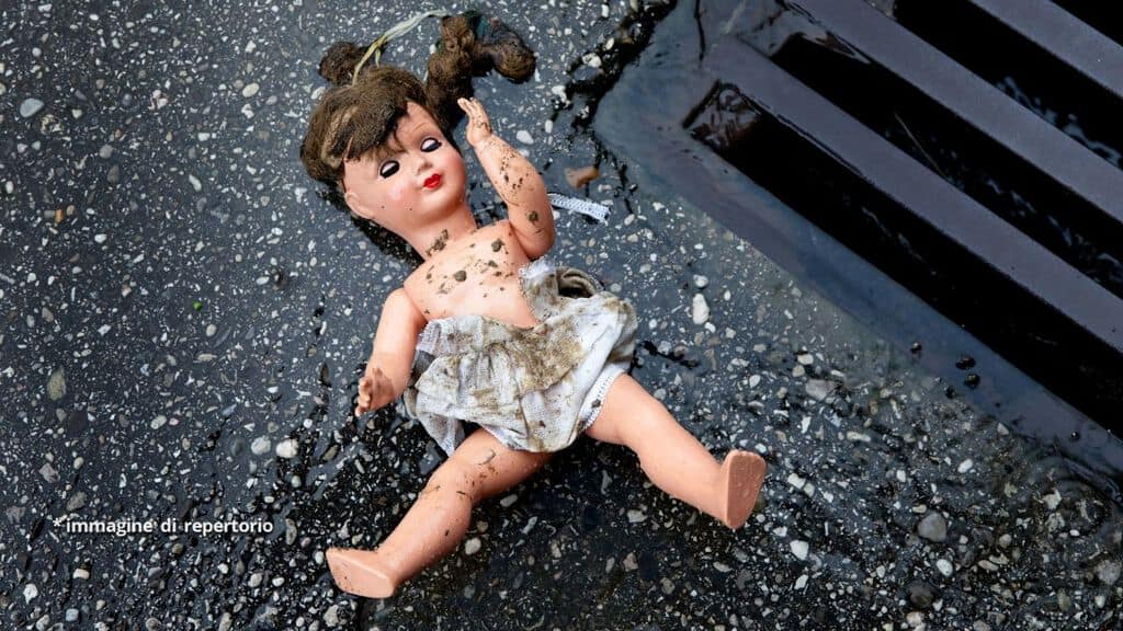 bambola a terra vicino a un tombino