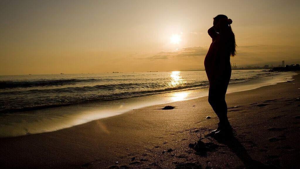 Donna in gravidanza sul bagnasciuga