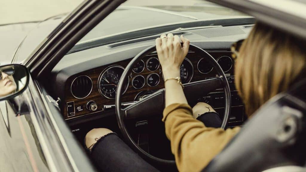 mani di donna al volante inquadrate da dietro