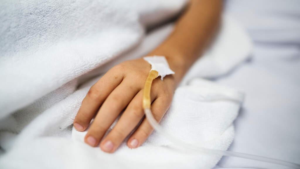mano in letto di ospedale con flebo